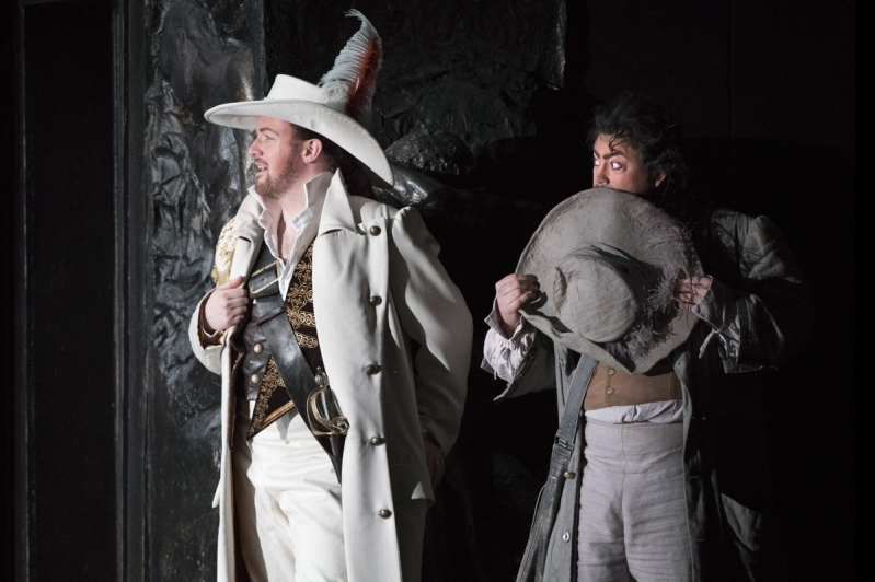Don Giovanni and Leporello stand close together, looking tentatively to their right.