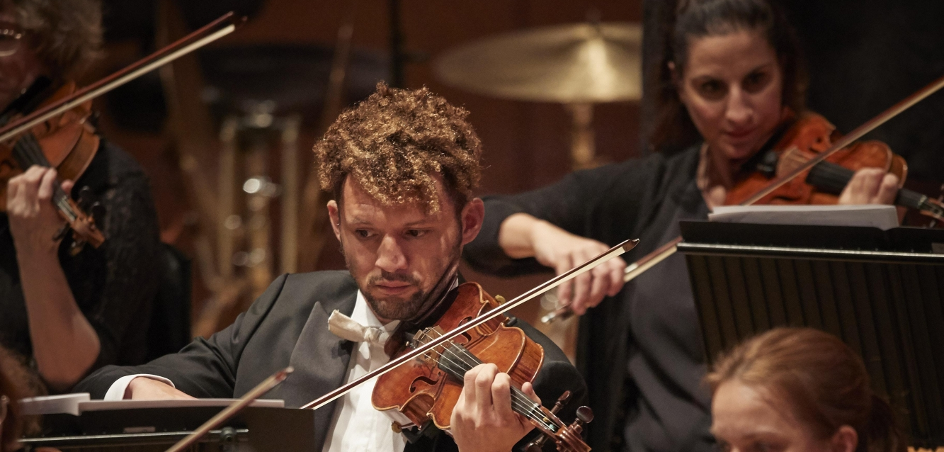 Close-up of three violinists from the WNO orchestra