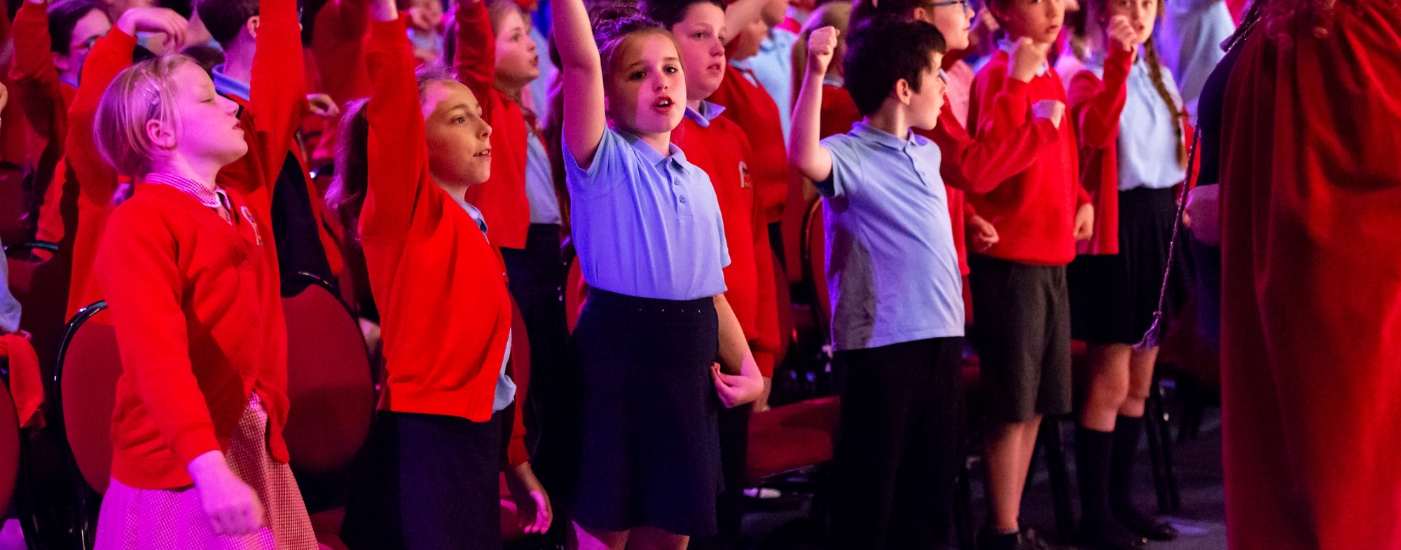 A large group of Primary School children in red and blue uniforms sing, some with arms in the air. Black box rehearsal room setting.