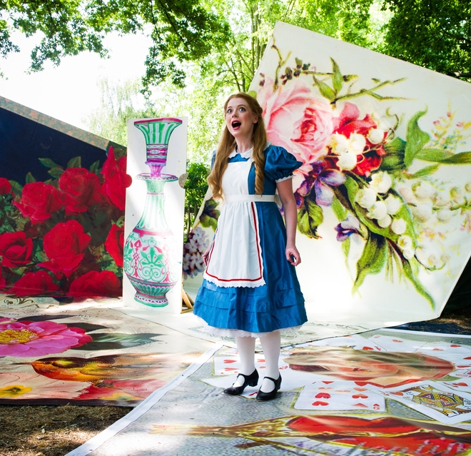 Surrounded by plants and flowers, Alice looking rejoiced at being in Wonderland,