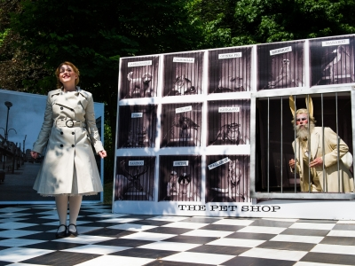Alice standing in the pet shop, lost in a daydream, with the White Rabbit in a cage behind her