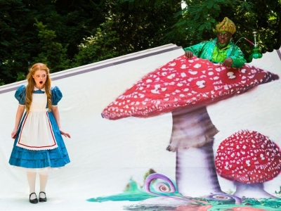 Alice looking shocked in Wonderland with a large mushroom next to her