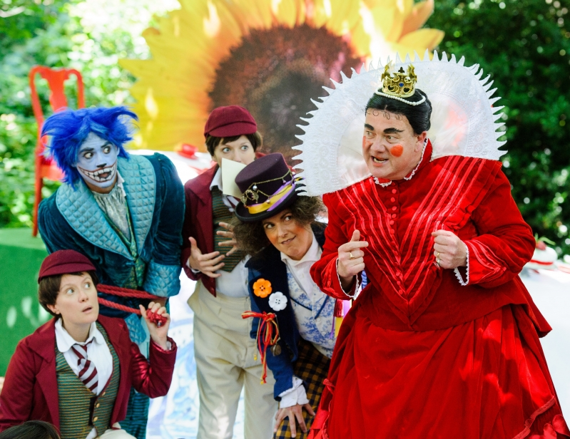 Queen of Hearts, Mad Hatter, Cheshire Cat and two young boys looking intrigued in Wonderland