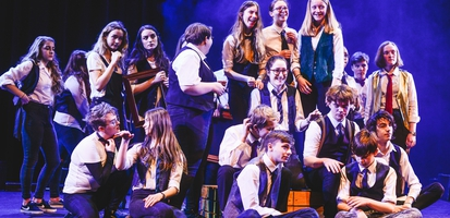 Cast of the youth orchestra are gathered on stage, looking happy.
