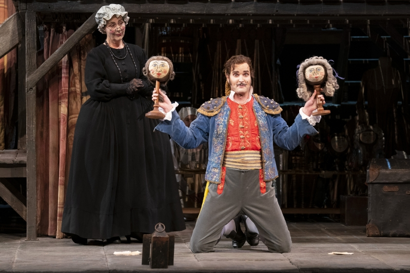 Figaro kneeling on stage with two puppets, Bag lady stood behind him