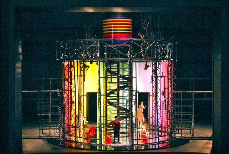 People dressed in gold and read top hat and tails are still in the prison. The lighting is bright and multi-coloured - like a rainbow.